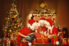 Los niños de la Navidad abren la actual caja de regalo, niños felices, árbol de Navidad Fotografía de archivo libre de regalías
