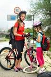 Los niños de las muchachas que completan un ciclo a la familia bombean para arriba el neumático de la bicicleta Imagen de archivo
