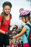 Los niños de las muchachas que completan un ciclo a la familia bombean para arriba el neumático de la bicicleta Fotografía de archivo
