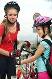 Los niños de las muchachas que completan un ciclo a la familia bombean para arriba el neumático de la bicicleta Fotografía de archivo libre de regalías