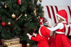 Los niños de Papá Noel adornan un árbol de navidad Fotografía de archivo