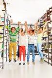 Los niños de risa saltan con las manos para arriba en la biblioteca Foto de archivo