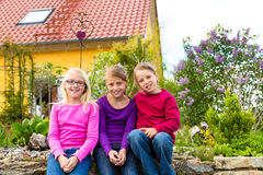Los niños de risa se sientan delante de la casa en el jardín Fotografía de archivo