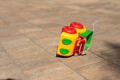 Los ni?os del beb? juegan el fondo: el coche coloreado juguete golpe? encima en la piedra de pavimentaci?n foto de archivo libre de regalías