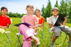 Los niños del dibujo se sientan en las sillas blancas afuera Fotografía de archivo libre de regalías