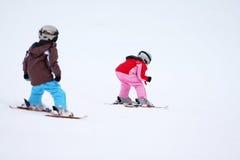 Los niños del invierno esquían en nieve Foto de archivo