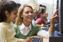 Los niños del jardín de la infancia aprenden cómo utilizar los ordenadores imagen de archivo