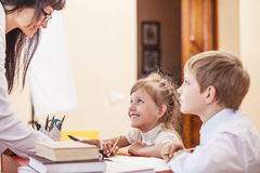 Los niños del muchacho y de la muchacha con el profesor en la escuela tienen un feliz fotografía de archivo