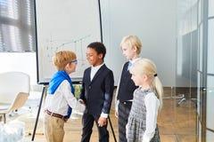 Los niños del negocio se saludan con un apretón de manos fotografía de archivo libre de regalías