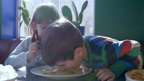 Los niños desayunan, los niños alegres que comen las crepes en cantina contra ventana metrajes