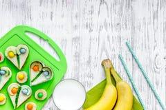 Los niños desayunan con los bocadillos y las frutas divertidos en copyspace de madera ligero de la opinión superior del fondo de  Foto de archivo libre de regalías