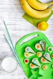 Los niños desayunan con los bocadillos y las frutas divertidos en copyspace de madera ligero de la opinión superior del fondo de  Fotografía de archivo