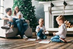 Los niños dibujan a los marcadores en piso mientras que los padres relajan el sofá Imagen de archivo libre de regalías