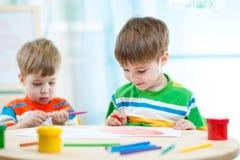 los niños dibujan y pintan en casa o centro de cuidado de día Imagen de archivo