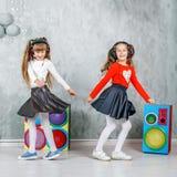 Los niños divertidos bailan y escuchan la música en auriculares El concentrado Imágenes de archivo libres de regalías