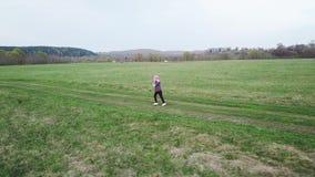 Los niños divertidos corren alrededor del campo verde en la primavera metrajes
