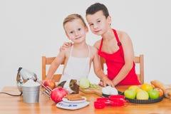 Los niños divertidos de la familia feliz están preparando la empanada de manzana, en un fondo blanco fotos de archivo