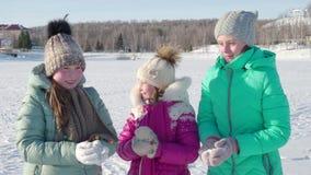 Los niños divertidos en casquillos y manoplas lanzan nieve para arriba en invierno 4K almacen de video