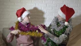 Los niños divertidos en los sombreros de Papá Noel se adornan con las guirnaldas de la malla, del juego colorido y de la sonrisa  almacen de metraje de vídeo