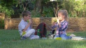 Los niños durante hendidura comen el almuerzo que se sienta cerca de las mochilas y los libros en el césped, el muchacho y la muc metrajes