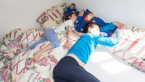 Los niños durmientes relajan resto de reclinación de los muchachos Imagen de archivo libre de regalías