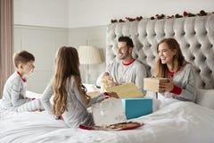 Los niños emocionados que se sientan en padres acuestan en casa como regalos abiertos de la familia el día de la Navidad fotos de archivo libres de regalías