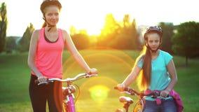 Los niños en casco de la bicicleta van en la bici del paseo de la colina almacen de metraje de vídeo