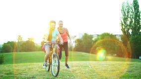 Los niños en casco de la bicicleta van en la bici del paseo de la colina almacen de video