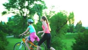 Los niños en casco de la bicicleta van en la bici del paseo de la colina metrajes