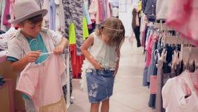 Los niños en compras, los pequeños compradores eligen la nueva ropa de moda en el boutique costoso almacen de metraje de vídeo