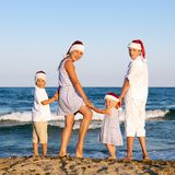 Los niños en el sombrero de Papá Noel se están colocando en la playa Fotos de archivo