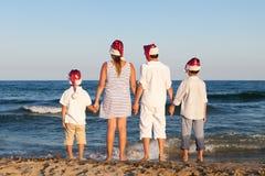 Los niños en el sombrero de Papá Noel se están colocando en la playa Imagenes de archivo