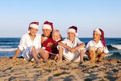 Los niños en el sombrero de Papá Noel se están sentando en la playa Imágenes de archivo libres de regalías