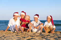 Los niños en el sombrero de Papá Noel se están sentando en la playa Fotos de archivo libres de regalías