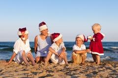 Los niños en el sombrero de Papá Noel se están sentando en la playa Imagen de archivo
