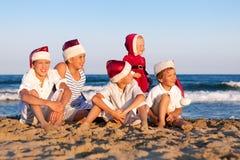 Los niños en el sombrero de Papá Noel se están sentando en la playa Foto de archivo libre de regalías