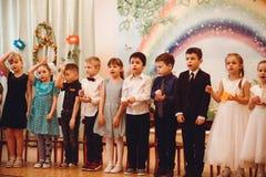 Los niños en equipos hermosos celebran el banquete de la primavera en guardería imagen de archivo
