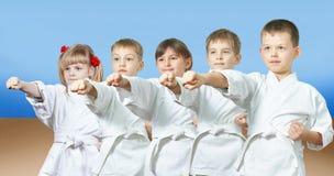 Los niños en karategi están golpeando el brazo del sacador fotografía de archivo libre de regalías