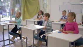 Los niños en la escuela, los muchachos y las muchachas se sientan en los escritorios y aumentan las manos durante la lección en s almacen de video