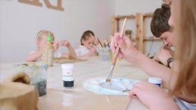 Los niños en la lección del arte en escuela primaria son de pintura y que esculpen de la arcilla almacen de video