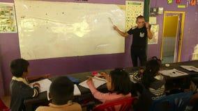 Los niños en la lección en la escuela del camboyano del proyecto embroman cuidado almacen de metraje de vídeo