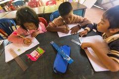 Los niños en la lección en la escuela del camboyano del proyecto embroman cuidado Imágenes de archivo libres de regalías