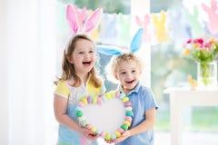 Los niños en oídos del conejito en el huevo de Pascua cazan Imagen de archivo