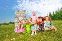 Los niños en trajes del festival se sientan en hierba Fotografía de archivo