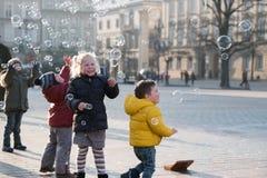 Los niños envejecen 4-5 años que juegan con las burbujas de jabón en el cuadrado Fotos de archivo