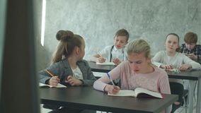 Los niños escuchan un profesor, contestan a preguntas y al trabajo sobre proyecto de la clase almacen de metraje de vídeo