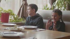 Los niños esperan la comida en un café de los alimentos de preparación rápida Familia elegante que se sienta en una mirada del sm almacen de metraje de vídeo