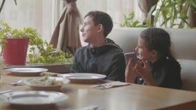 Los niños esperan la comida en un café de los alimentos de preparación rápida Familia elegante que se sienta en una mirada del sm almacen de video