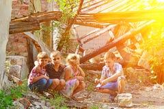 Los niños están cerca de la casa arruinada, del concepto de desastre natural, de fuego, y de devastación fotos de archivo