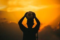 Los niños están jugando al fútbol del fútbol para el ejercicio bajo luz del sol Estilo de la imagen de la silueta y de la películ imagen de archivo